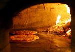 Lehmofenbau. Ein Lehmofen italienischer Bauart mit Pizzen.