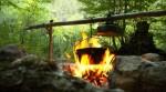 Kochen mit Feuer. Kochen outdoor. Eine Feuerstelle im Wald mit einem Kochtopf drauf.